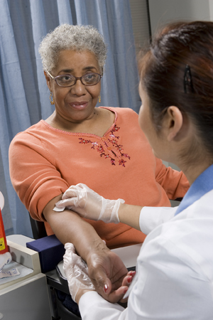 Health care provider taking blood sample from woman's arm.