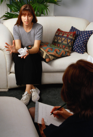 Woman sitting on sofa talking with counselor in office.