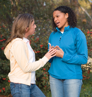 Two young women having a serious conversation outdoors.
