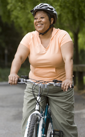 Overweight woman riding a bicycle on a country road.