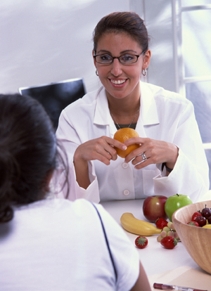 Healthcare provider talking to patient. There is a bowl of fruit on the table.