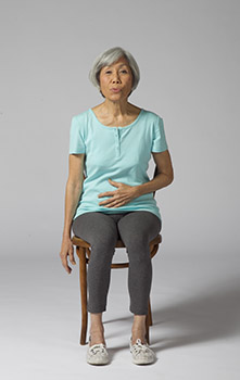 Woman sitting in a chair. She is practicing deep breathing exercises.