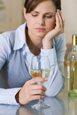 Woman with a glass of wine, looking depressed
