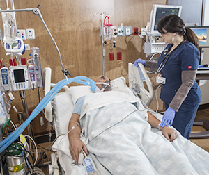 Patient lying in intensive care unit bed with medical machines surrounding him. Tube in his mouth from ventilator. Health care provider is standing by the bed.