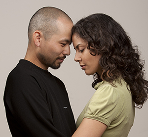 Man and woman standing with foreheads touching, holding each other.