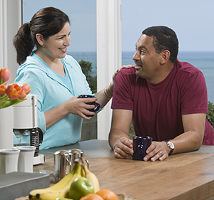 Couple talking at kitchen counter.