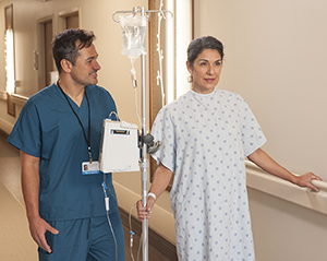 Walking soon after surgery helps prevent blood clots and breathWoman patient walking in hospital hall with an IV pole and nurse.ing problems.
