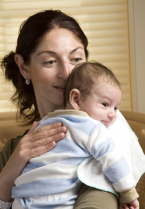 Woman holding baby over shoulder.