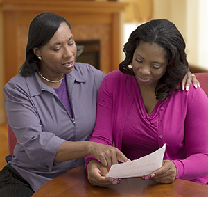 Two women looking at paperwork together.