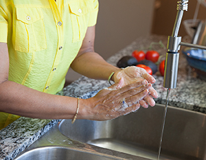 Closeup of woman washing hands in sink.