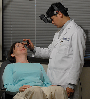 Healthcare provider examining woman's eyes.