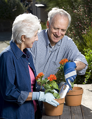 Woman and man planting flowers in pots.