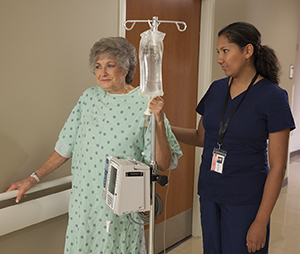 Patient walking in hosptial hallway with healthcare provider.