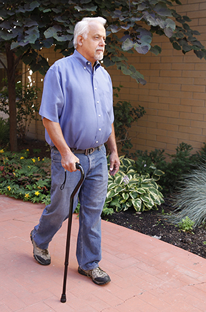 Man with cane walking outdoors.