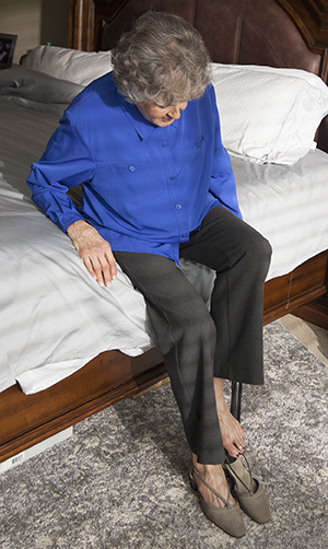 Woman sitting on bed putting on shoe with long-handled shoehorn.