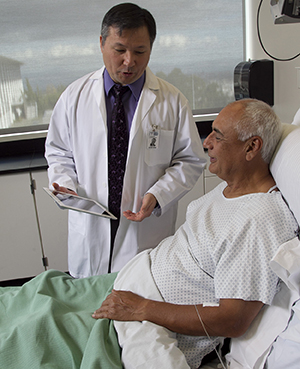 Healthcare provider with electronic tablet talking to man in hospital bed.