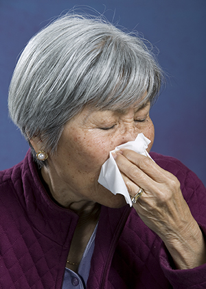 Woman holding tissue to nose.