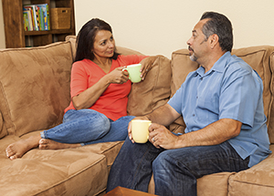 Man and woman sitting on couch, talking.