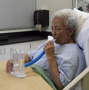 Woman wearing hospital gown using spirometer.