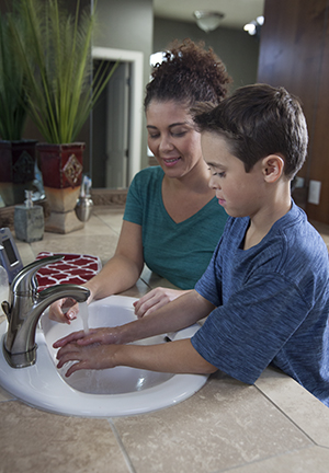 Woman helping boy wash hands.