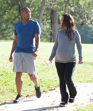 Man and pregnant woman walking in park.