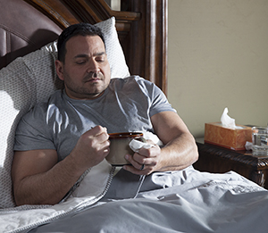 Man sitting in bed with a cup of soup.