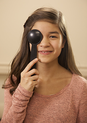 Girl holding cover over eye during eye exam.