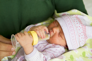 Newborn baby drinking from bottle.