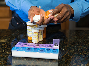 Closeup of man's hands filling pill organizer with medications.