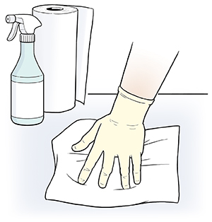 Gloved hand wiping surface with paper towel.
