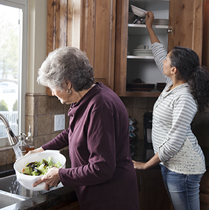 Woman reaching into upper shelf in kitchen cabinet while older woman makes salad.