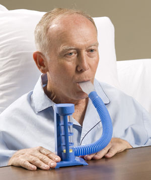 Man in hospital bed using incentive spirometer.