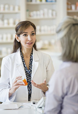 Pharmacist holding a bottle of pills and talking to woman in pharmacy.