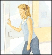 Image of woman bending knees slightly, leaning in and pushing against door